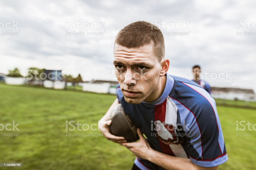 Determined rugby player running with ball on a playing field. Copy...