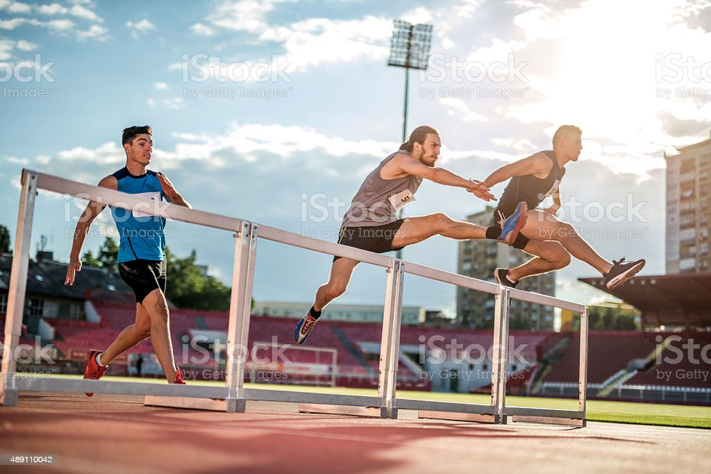 Determined athletes jumping hurdles on a sports race at stadium. stock photo