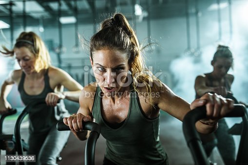 Young female athlete having cross training on bikes with her friends in a gym and looking at camera.