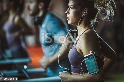Young female athlete running on treadmill in a gym and listening music over mobile phone.