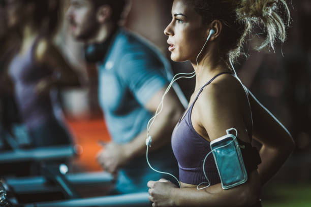 Determined athletic woman listening music while jogging on treadmill in a gym. Young female athlete running on treadmill in a gym and listening music over mobile phone. training equipment stock pictures, royalty-free photos & images