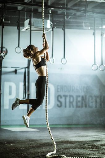 Strong female athlete moving up the rope during cross training in a health club.