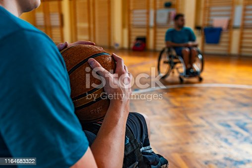 DIsabled sport men in action while playing indoor basketball at a basketball court. Sport Training of handicapped men in wheelchairs in sporthall during the day.