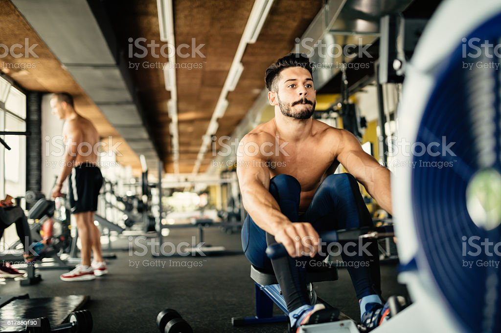 Determined bodybuilder rowing stock photo