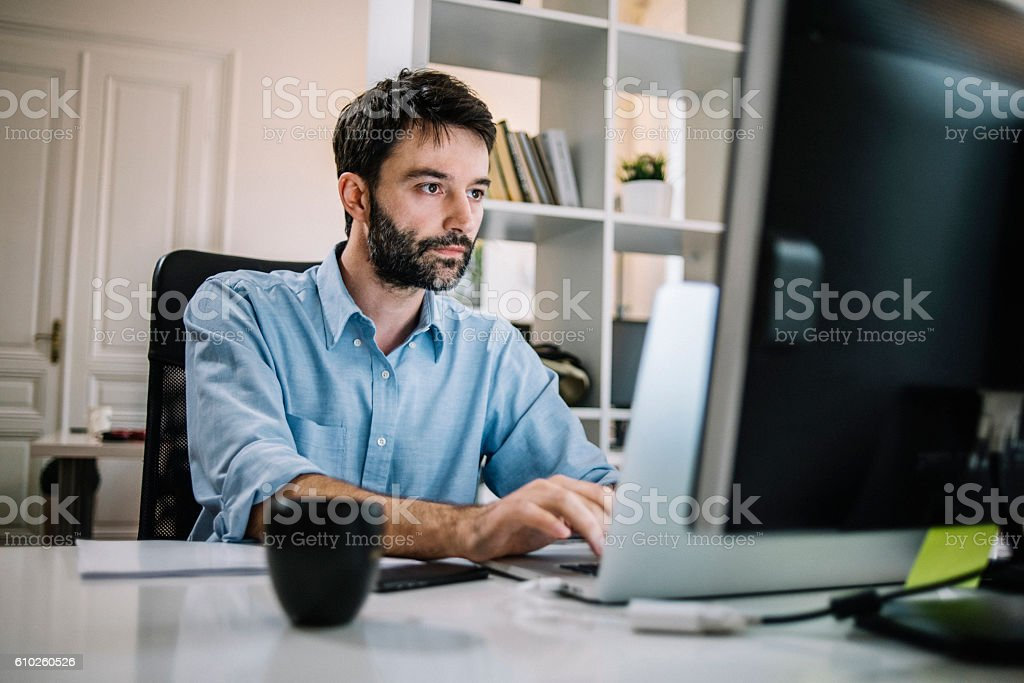 Determined businessman working on his computer stock photo