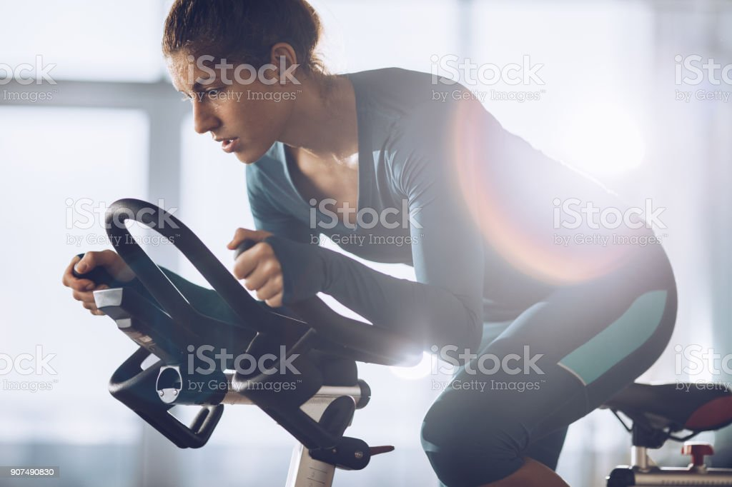 Determined female athlete on a spinning class in a health club. stock photo