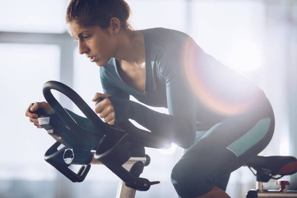 Determined female athlete on a exercising class in a health club. Athletic woman cycling on exercise bike during sports training in a gym. exercise bike stock pictures, royalty-free photos & images