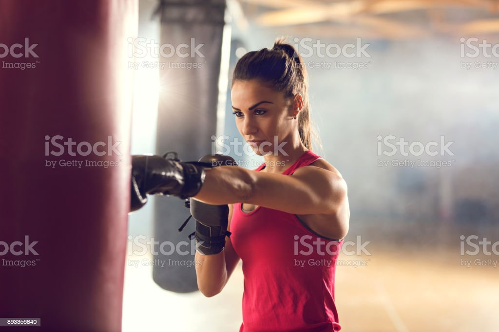 Determined female boxer exercising on a sports training in a health club. stock photo