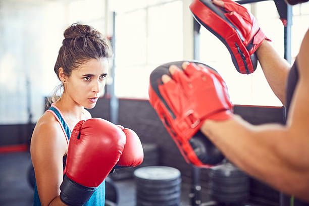 Determined female fit boxer practicing in gym – Foto