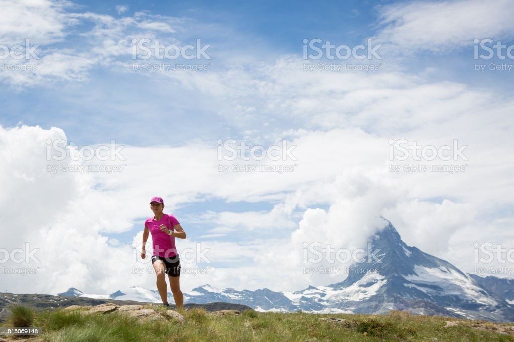 Determined female running in the mountains stock photo