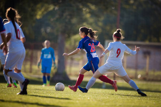 determined female soccer player in action during the match on playing field. - soccer competition stock photos and pictures