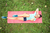 Determined fit young woman doing sit-ups in a park. Lying on a yoga mat, rising legs and head in the air. High angle view, directly from above. Active sport lifestyle in urban environment.