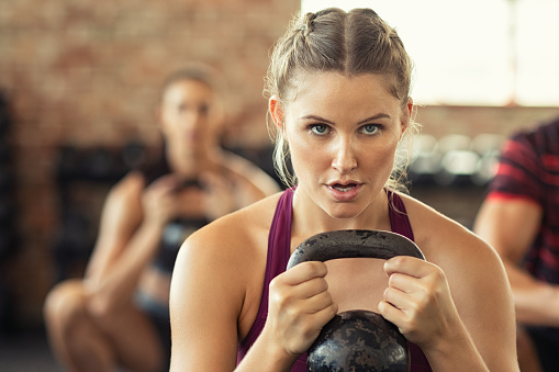 istock Determined fitness woman doing squat with kettle bell 1149242523