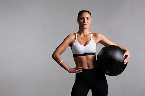 Portrait of beautiful mid adult woman looking at camera while holding heavy medicine ball isolated on grey background. Proud and fit woman standing on gray wall ready for gym exercise while looking at camera. Strong mixed race girl holding sports ball and relaxing after cross training workout with copy space.