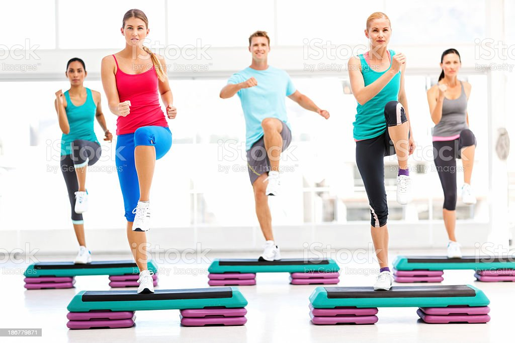 Determined Friends Doing Step Aerobics In Gym stock photo