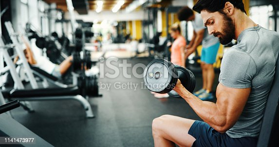 istock Determined handsome and young male working out in gym 1141473977