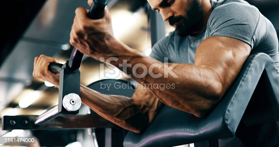 istock Determined handsome and young male working out in gym 1141474000