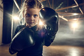 Little girl with boxing gloves standing in combat pose in a health club and looking at camera.