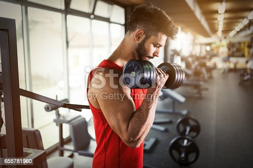 istock Determined male working out in gym lifting weights 655781960