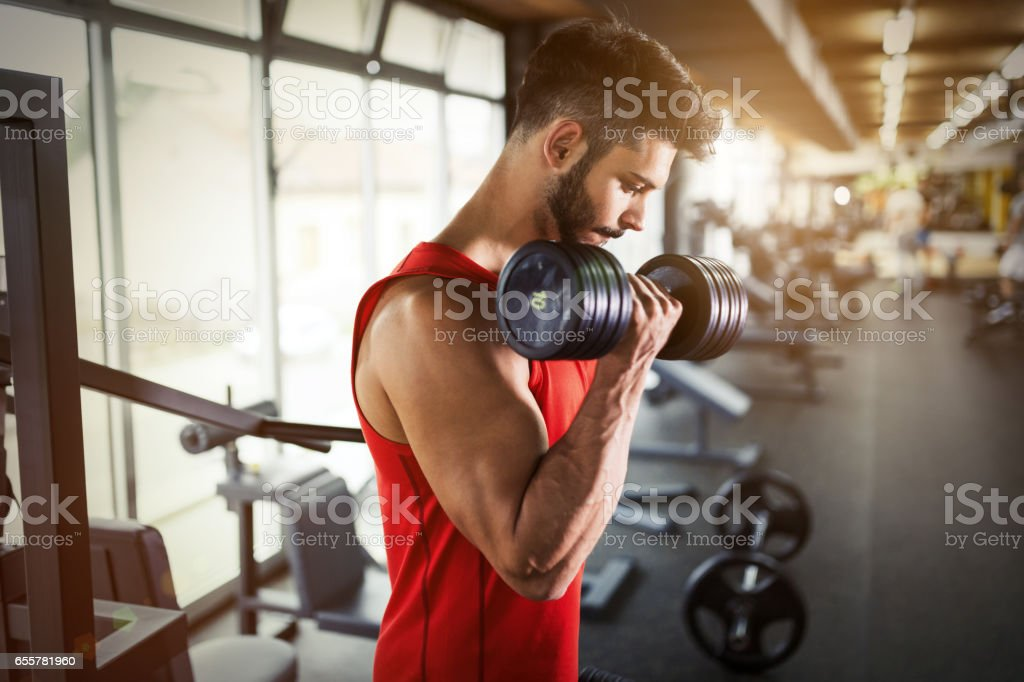 Determined male working out in gym lifting weights stock photo