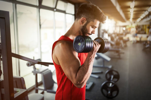 Determined male working out in gym lifting weights - foto de acervo