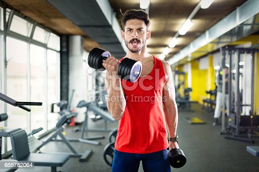 istock Determined male working out in gym lifting weights 655782064
