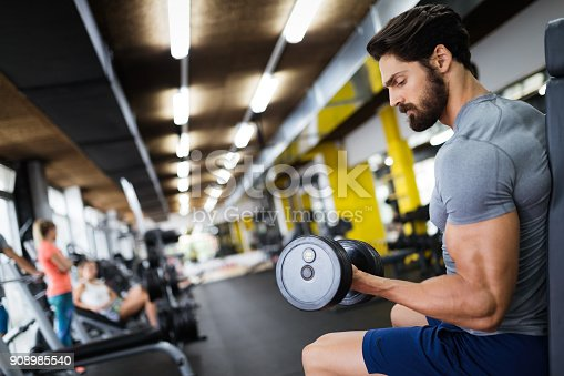 istock Determined male working out in gym 908985540