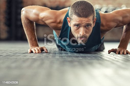 istock Determined man doing push ups at the gym 1149242526