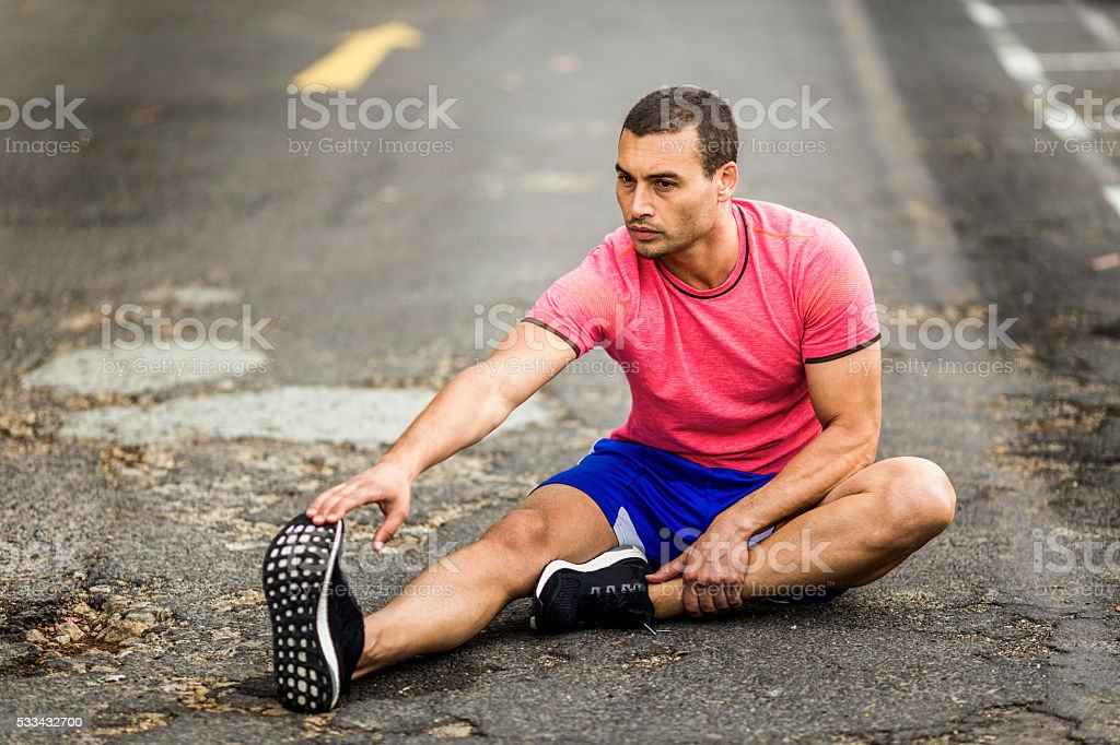 Determined man doing stretching exercise on road stock photo
