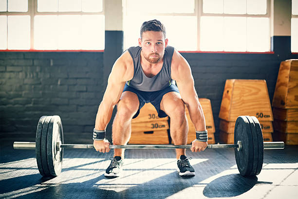 Determined man exercising while dead litfing barbell in gym – Foto