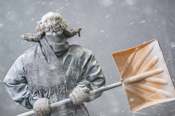 Determined man headed out to shovel snow in a blizzard stock photo