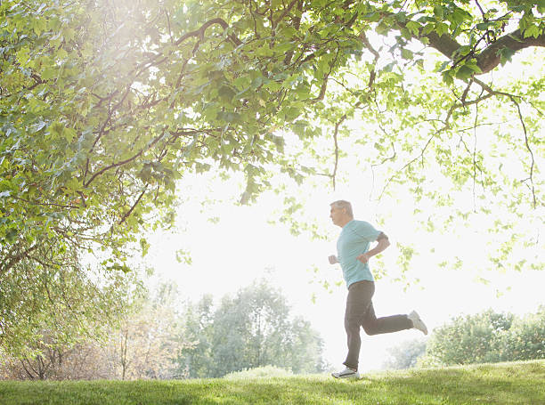Determined man jogging outdoors stock photo