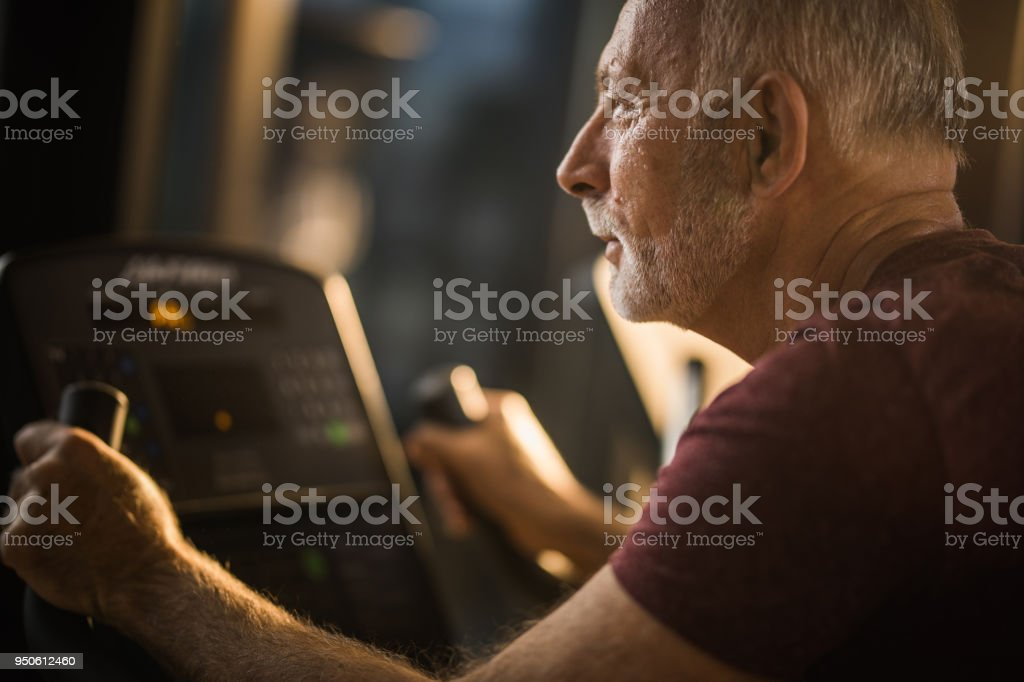 Determined mature man having a sports training on exercise bike in a health club. stock photo