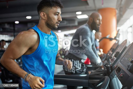 1069872470istockphoto Determined mature man running on treadmill in gym 1060199488
