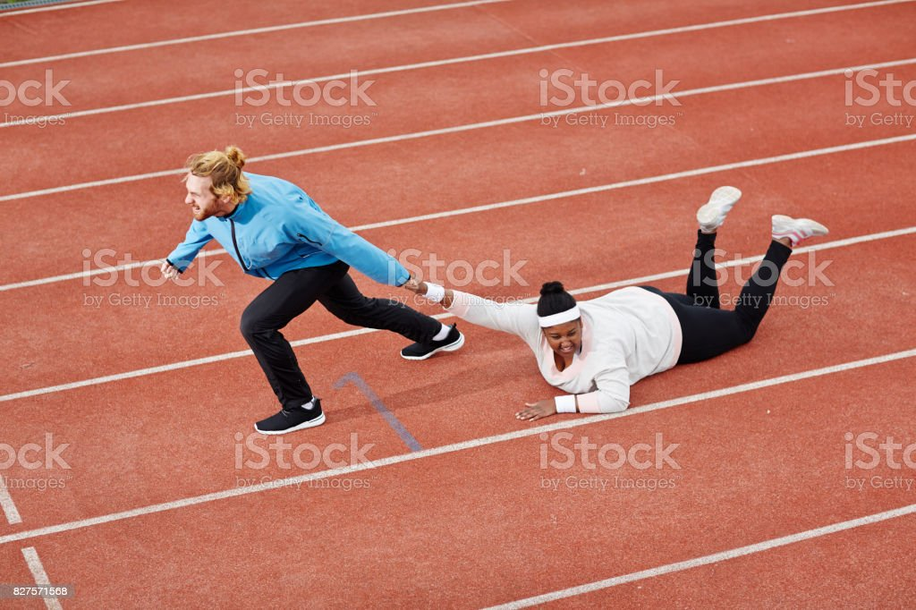 Determined personal trainer dragging exhausted overweight woman on track motivating her to keep running stock photo
