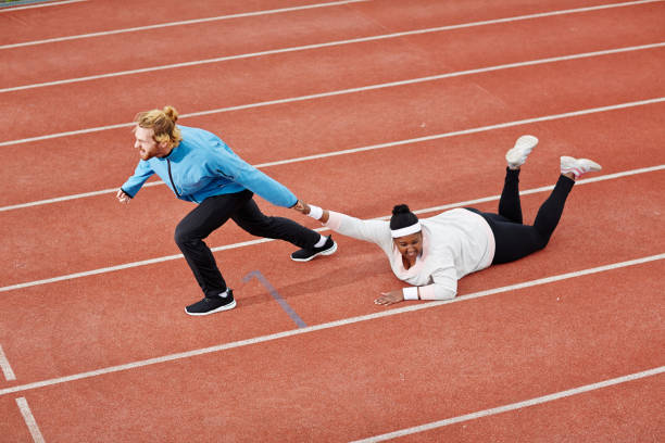 determined personal trainer dragging exhausted overweight woman on track motivating her to keep running - funny fat lady stock photos and pictures