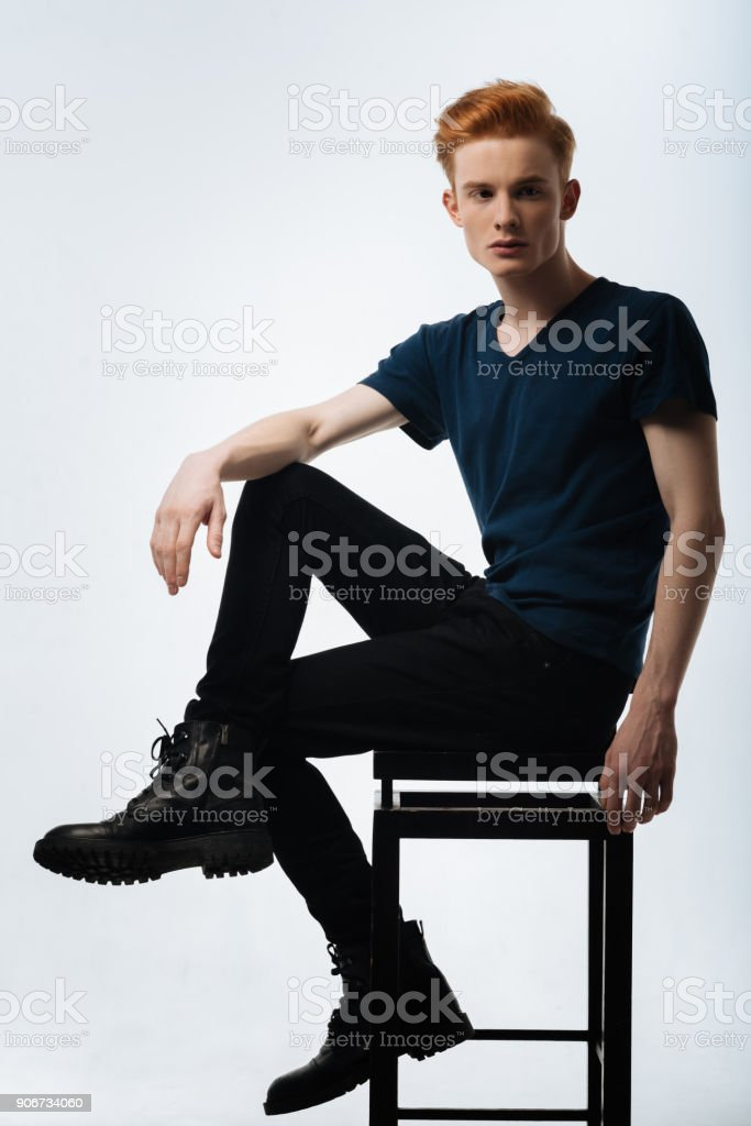 Determined red-headed young man sitting on the chair stock photo