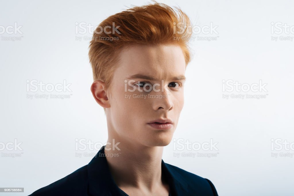 Determined red-headed young man staring stock photo