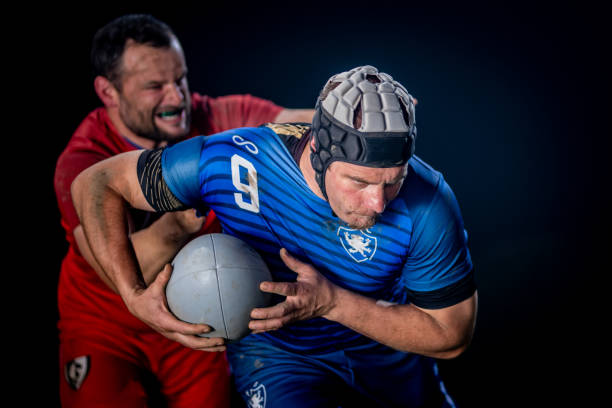 Determined rugby player running with the ball while getting tackled from behind