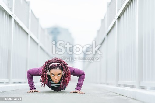 A determined sports woman is doing push-ups in the city.