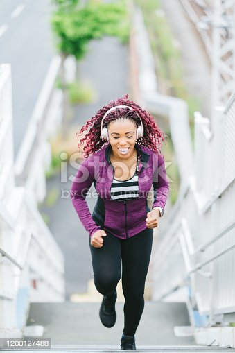 A determined sports woman is running up stairs with great effort.