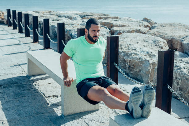 Determined Sporty Man Doing Triceps Dips on Benches stock photo