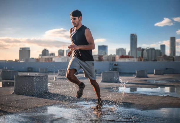 Entschlossener sportlicher junger Mann joggen auf Terrasse – Foto