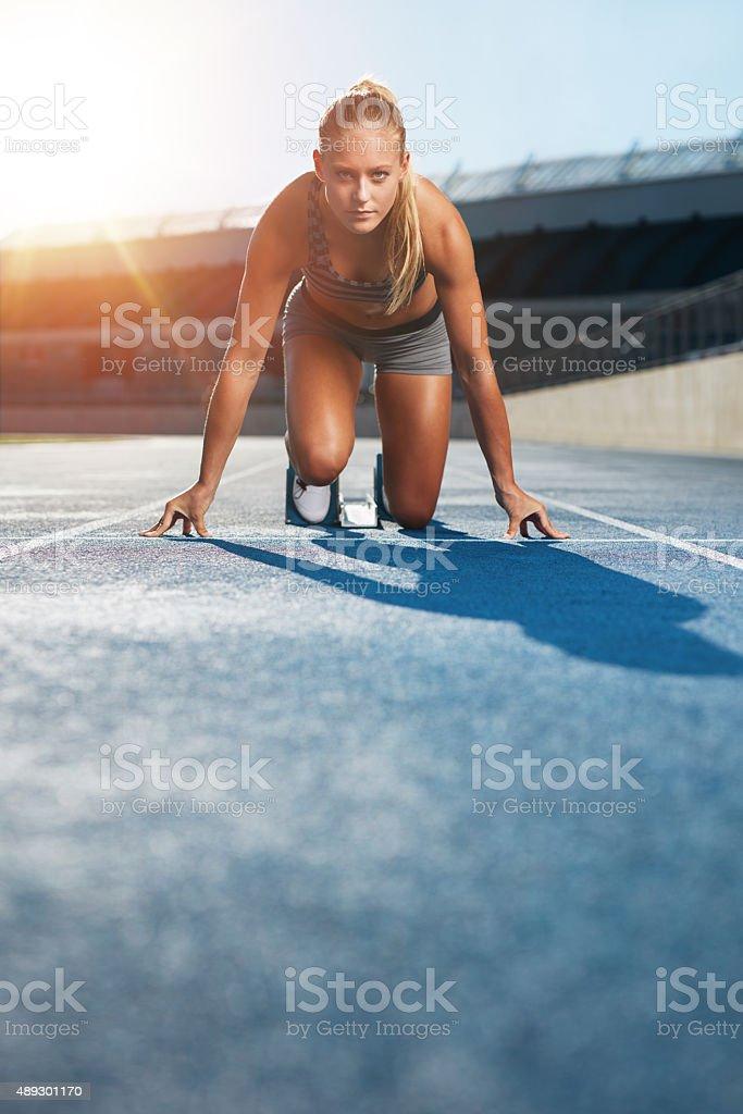 Determined sprinter at starting block stock photo