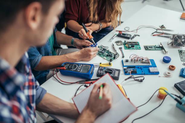 entschlossenen studenten ingenieure - freizeitelektronik stock-fotos und bilder