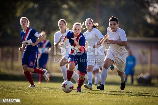 istock Determined teenage girl running with ball on a soccer match against her opponents. 857392758