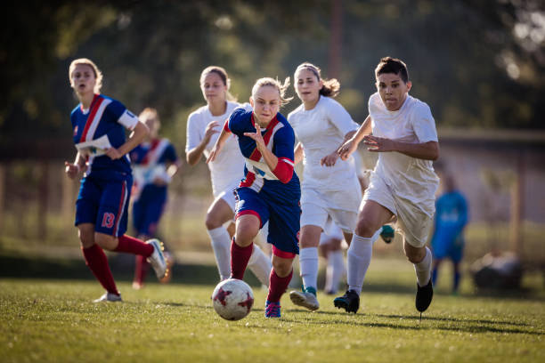 Determinado adolescente correndo com a bola em um jogo de futebol contra seus oponentes. - foto de acervo