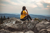 Girl sitting on a green meadow and watching the countryside landscape at evening landscape in southern Germany on the Feldberg 1493m. the highest mountain in the state of baden-württemberg.