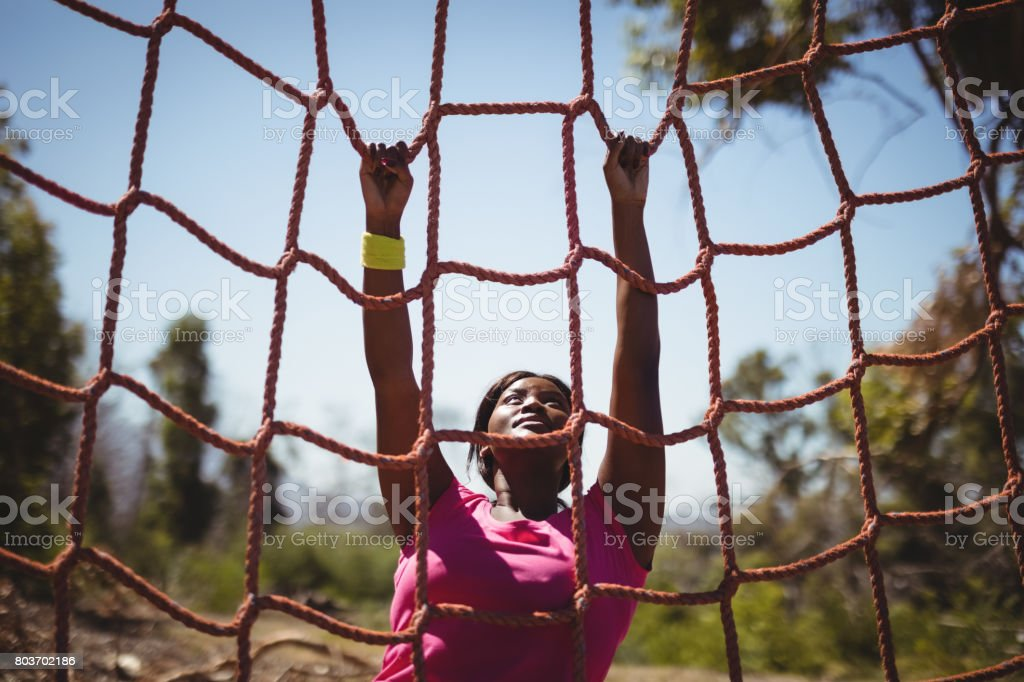 Entschlossenen Frau, die ein Netz während der Hindernis-Parcours klettern – Foto