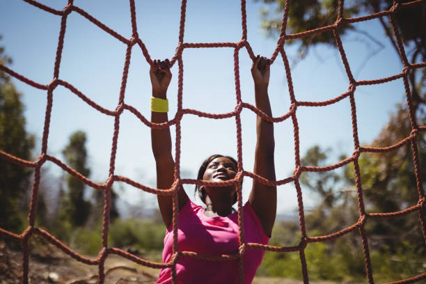 determined woman climbing a net during obstacle course - campo militar imagens e fotografias de stock